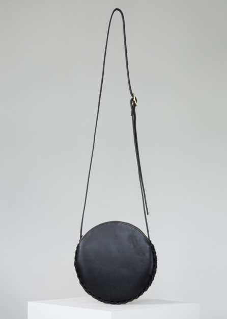 This Annoukis black leather bag is handmade from vegetable tanned leather, featuring calf suede lining, a brass buckle with adjustable straps, and a YKK zipper