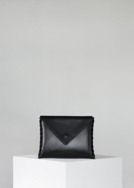 This Annoukis black leather clutch is handmade from vegetable tanned leather, featuring calf suede lining, a brass buckle, and a magnetic snap