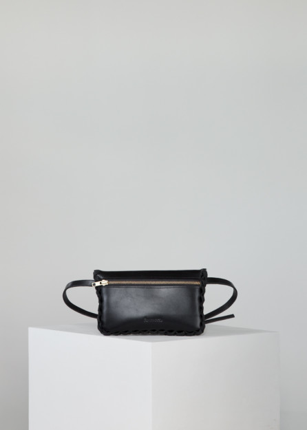 This Annoukis black leather bag is handmade from vegetable tanned leather, featuring calf suede lining, a brass buckle, and a YKK zipper